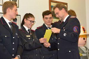 Jugendwart Manfred Köncke überreicht den vollgeschriebenen Jugendfeuerwehrausweis an Leonie.
