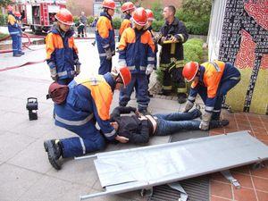 Eine Person wurde vom Angriffstrupp aus dem Gebäude gebracht und wird jetzt zur Verletztensammelstelle getragen.